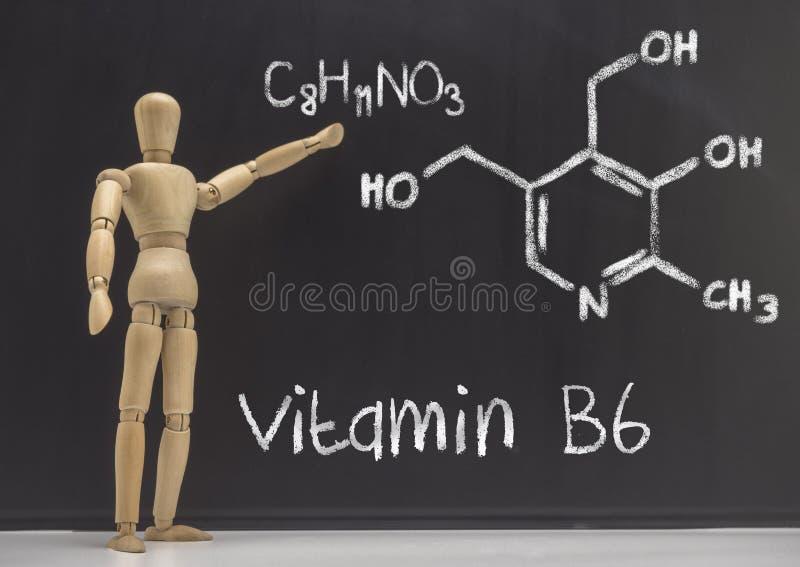 Den artikulerade dockan undervisar i en svart tavla den kemiska sammansättningen av vitaminet B6 arkivbilder