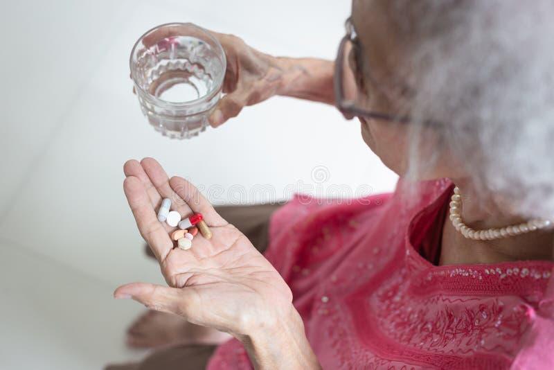 Den asiatiska äldre kvinnan är ta och äta mediciner och vitaminer royaltyfri bild