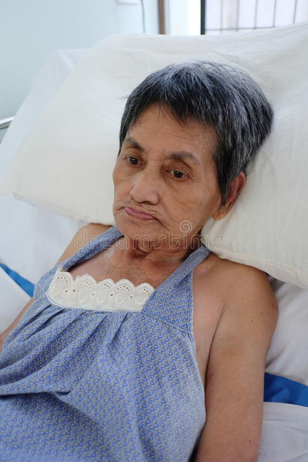 Den asiatiska äldre kvinnan lägger sjukt på säng arkivfoto