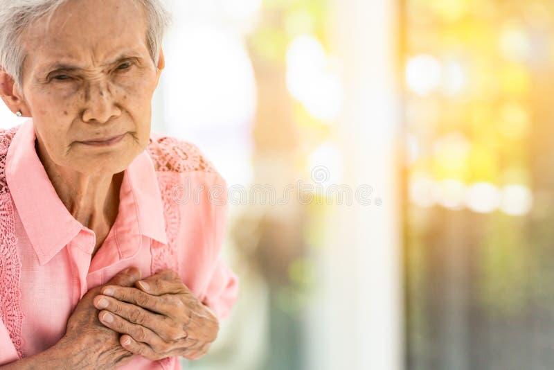 Den asiatiska äldre kvinnan med bestämda tecken, svårighet som andas, lidande eller hjärtaproblem, meddelar tecknen av hjärta royaltyfri bild