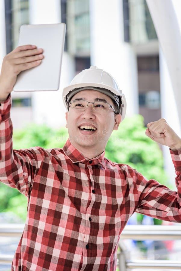 Den asiatiska affärs- och teknikermannen med den röda scott skjortan har plannin arkivbild