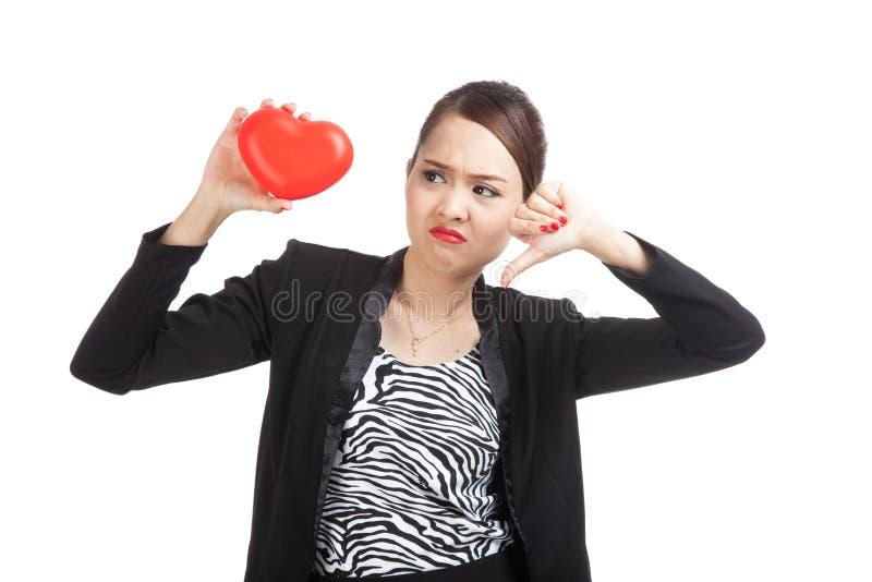 Den asiatiska affärskvinnan tummar ner med röd hjärta arkivfoto