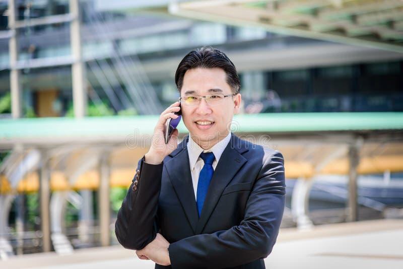 Den asiatiska affärsmannen har arbete på mobil med lyckligt royaltyfri foto
