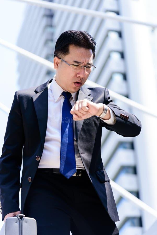Den asiatiska affärsmannen har innehavet en svart påse och att se på klockan, i att skynda sig tid arkivfoton