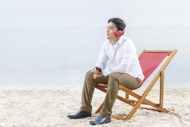 Den asiatiska affärsmannen kopplar av, när han arbetar med mobiltelefonstund genom att använda hörlurar som sitter i strandstolen royaltyfri fotografi