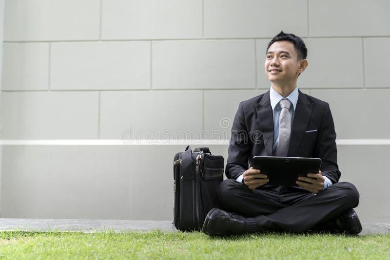 Den asiatiska affärsmannen som använder den bärbara datoren parkerar på, av stad arkivfoton