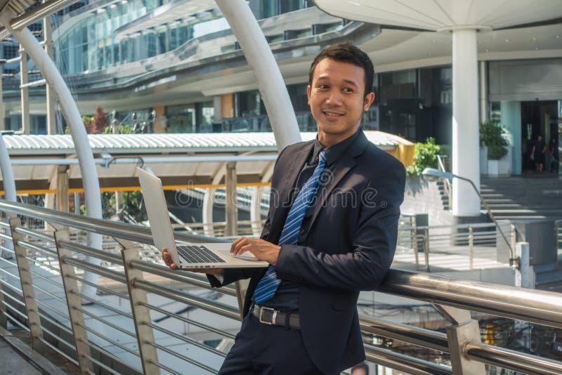 Den asiatiska affärsmannen som rymmer en bärbar dator, kontrollerar informationen royaltyfria foton