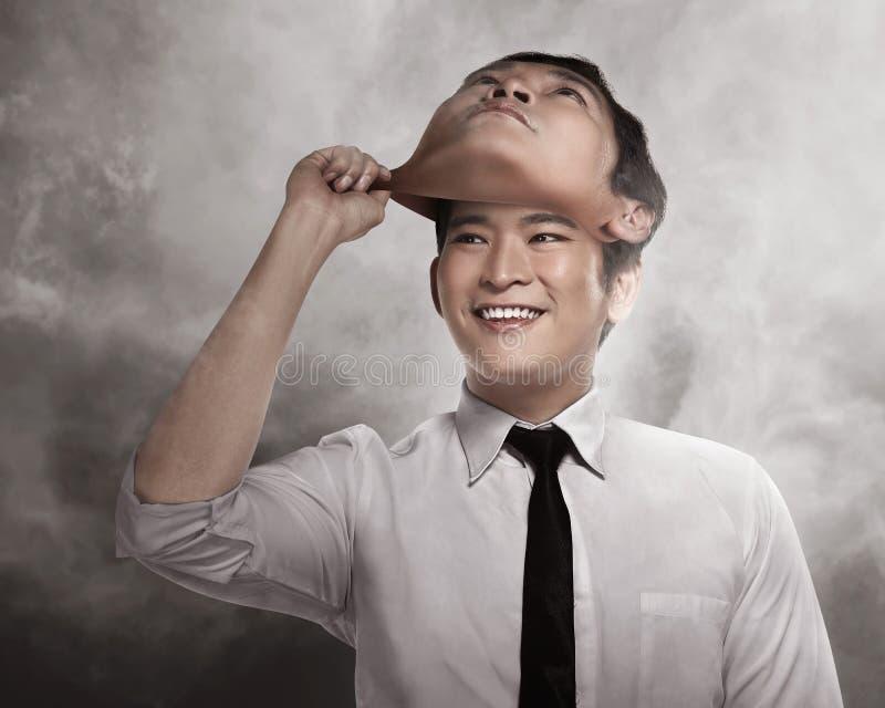Den asiatiska affärsmannen tar bort hans annan framsidamaskering arkivbild