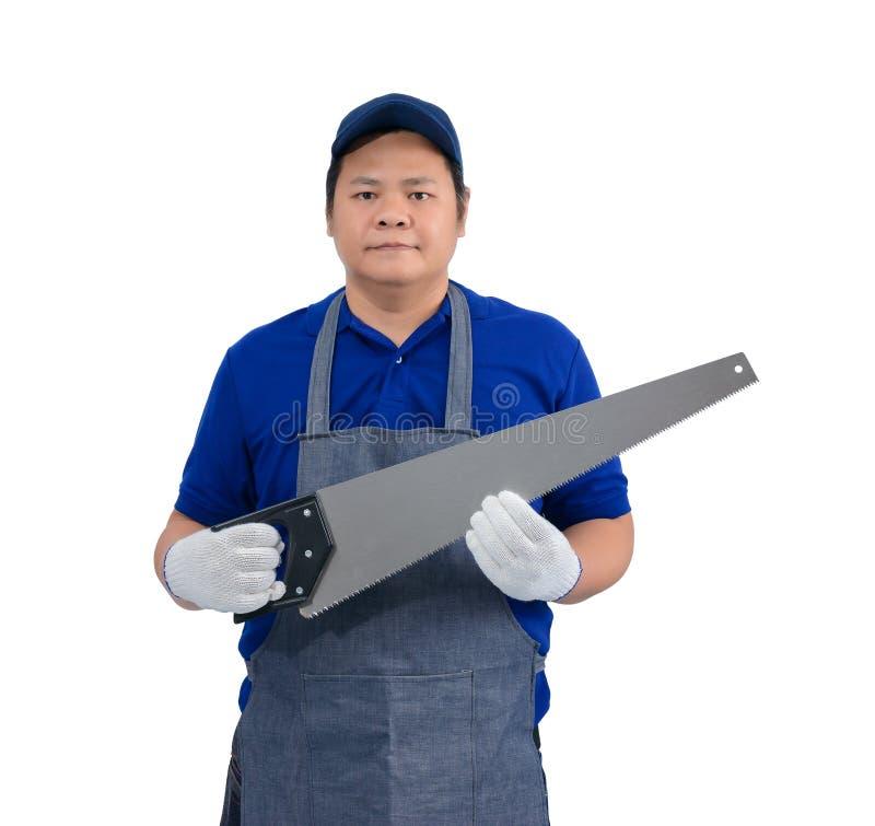 Den asiatiska arbetarmannen i blå skjorta med förklädet och skyddande handskar räcker innehavet såg isolerat på vit royaltyfri bild