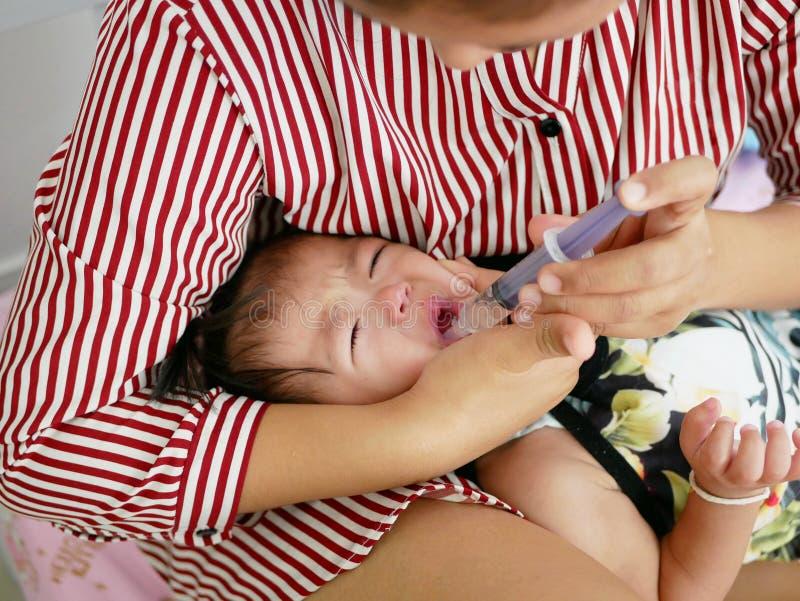 Den asiatiska armen för moder` som s slår in runt om hennes skriande, behandla som ett barn framsidan för flicka` som s tvingar b royaltyfria foton