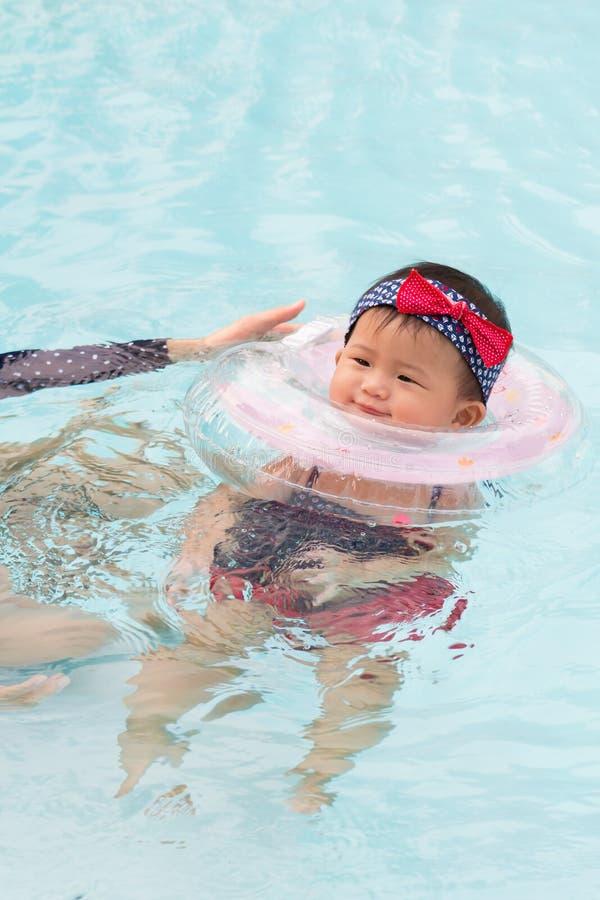 Den asiatiska barnmodern och den gulliga åtta månaden behandla som ett barn att tycka om simma p royaltyfria foton