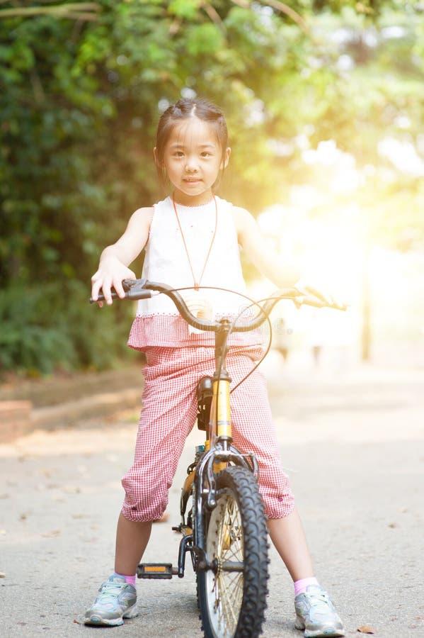 Den asiatiska barnridningen cyklar utomhus- royaltyfri fotografi