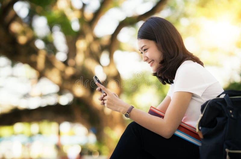 Den asiatiska damen kopplar av med den smarta telefonen för mobilen royaltyfri bild