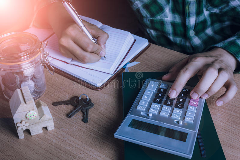 Den asiatiska den manrevisorn eller bankiren beräknar finanser/besparingar pengar eller ekonomi för hyrahem