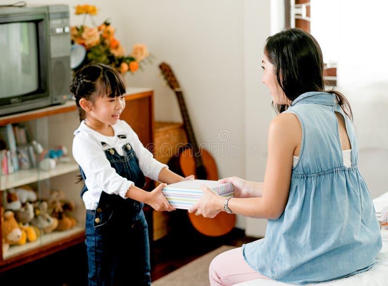 Den asiatiska dottern ger gåvaasken till hennes moder med förälskelse i sovrum och något möblemang som bakgrund arkivfoton