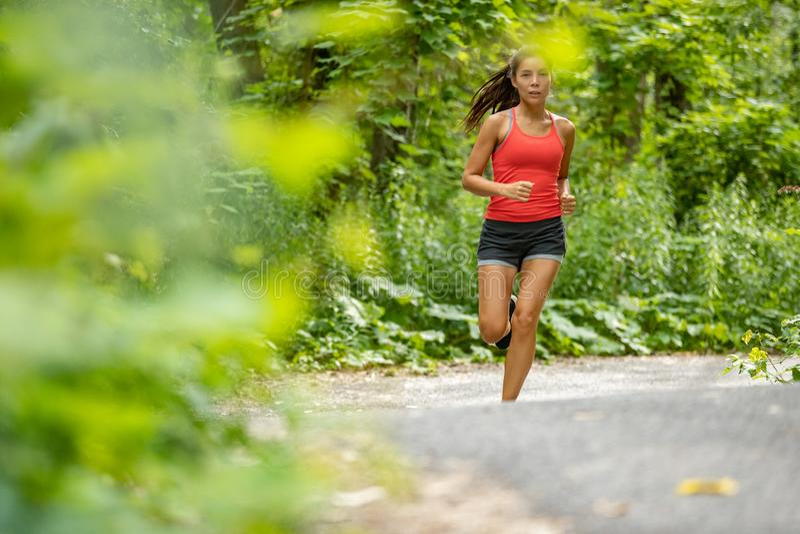 Den asiatiska färdiga flickan som in joggar, parkerar Ung kvinna som kör på utbildning för övning för natur för skogbana cardio u fotografering för bildbyråer