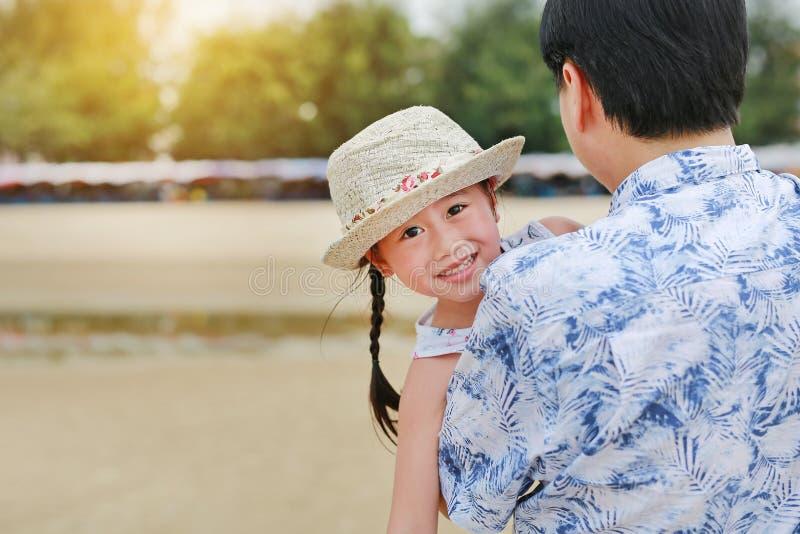 Den asiatiska fadern bär hans dotter som ler på stranden arkivbild