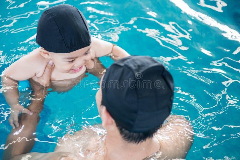 Den asiatiska fadern och behandla som ett barn kurssimbassängen i vatten royaltyfri foto