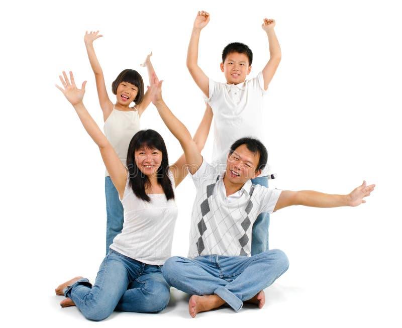 Den asiatiska familjen arms upp royaltyfria bilder