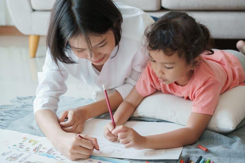 Den asiatiska familjen med modern och döttrar drar på papper hemma Föräldrar undervisar flickan att dra med färger på vitbok arkivfoton