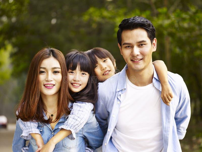 Den asiatiska familjen som in går, parkerar arkivfoto