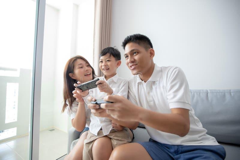 Den asiatiska familjen som har den roliga spela datorkonsolen, spelar tillsammans, royaltyfri bild