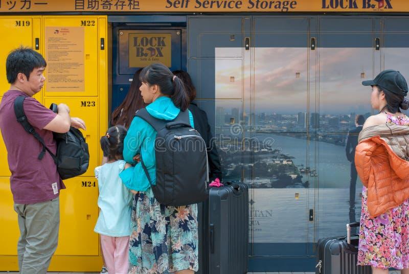 Den asiatiska familjen står framme av gul självbetjäninglagring fotografering för bildbyråer