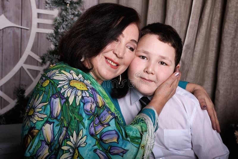 Den asiatiska familjfarmodern kramar sonsonen arkivbild