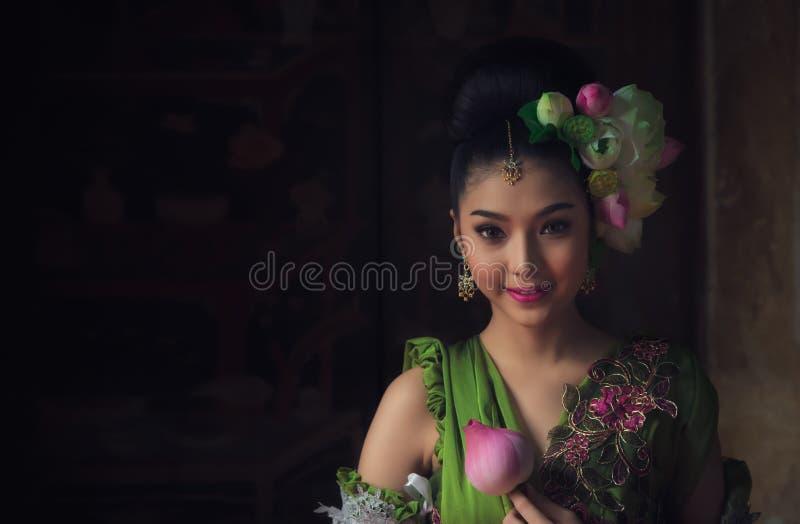 Den asiatiska felika gudinnan smyckade med lotusblommablommor, henne log royaltyfria foton