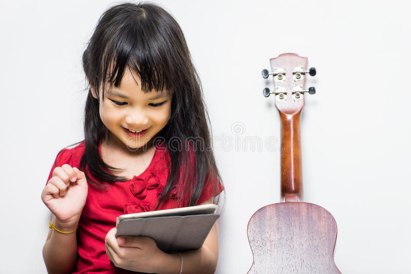 Den asiatiska flickan använder hennes minnestavla för att lära att spela musik royaltyfri fotografi