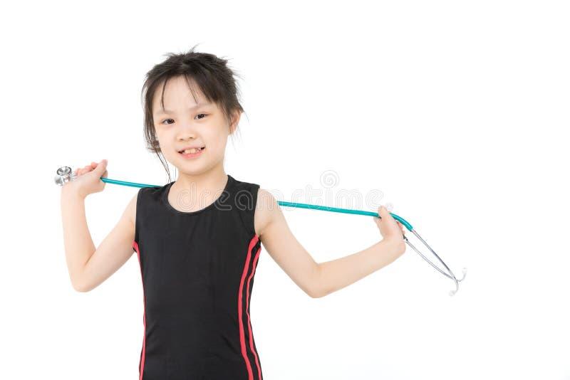 Den asiatiska flickan b?r gr?n stechoscope royaltyfria bilder