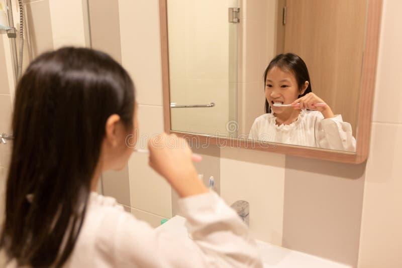 Den asiatiska flickan borstar hennes tänder och ler, medan se i th royaltyfri foto
