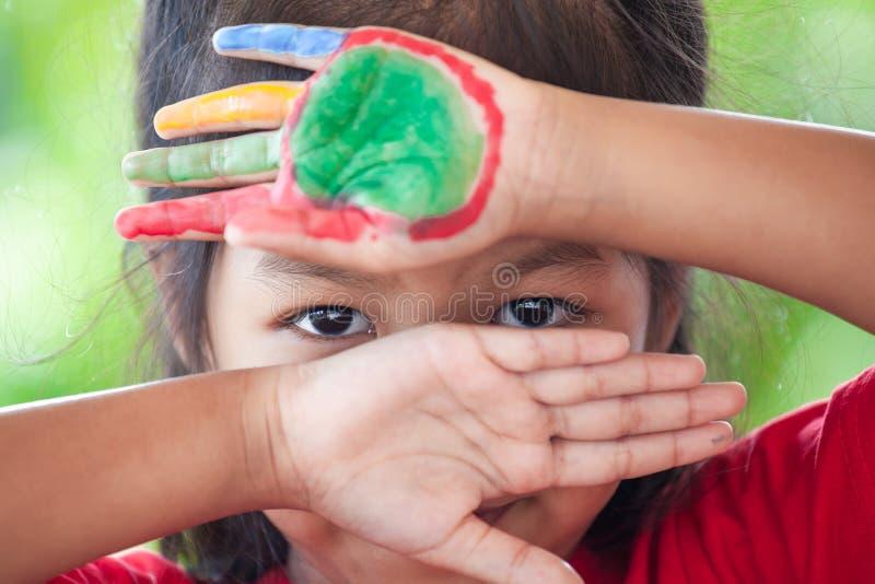 Den asiatiska flickan för det lilla barnet med målade händer stängde hennes framsida och uppvisning endast av hennes ögon royaltyfri foto
