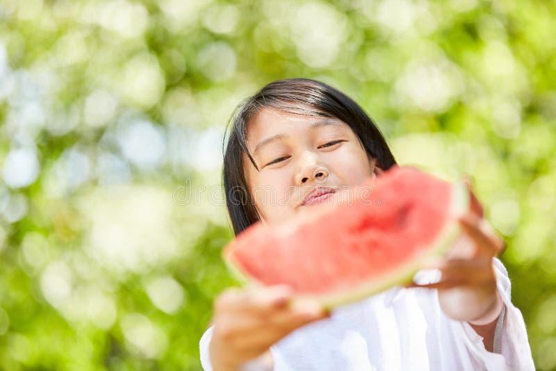 Den asiatiska flickan fördelar ett stycke av vattenmelon royaltyfria bilder