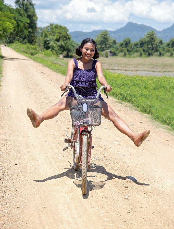 Den asiatiska flickan går på en cykel arkivbild
