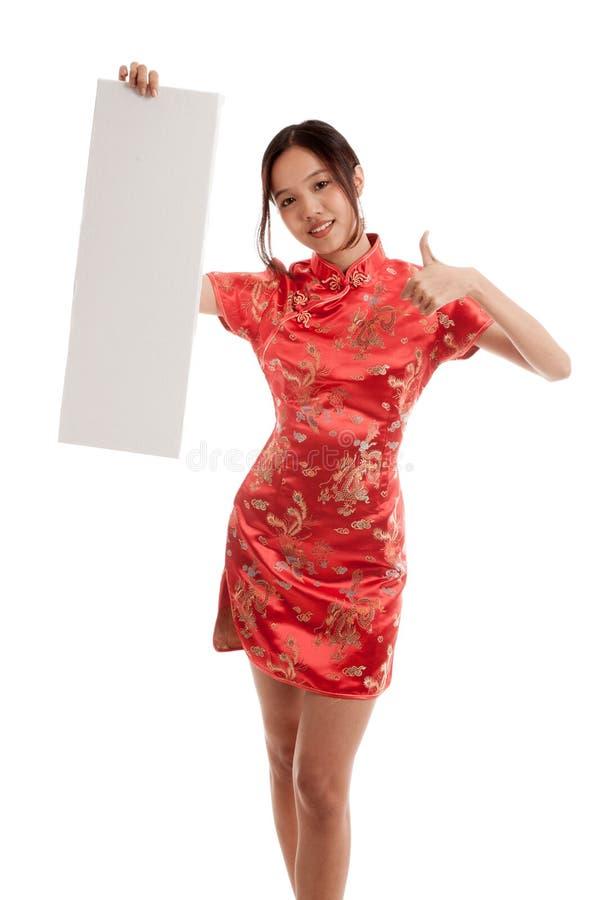 Den asiatiska flickan i kinesisk cheongsamklänning tummar upp med det tomma tecknet arkivbild