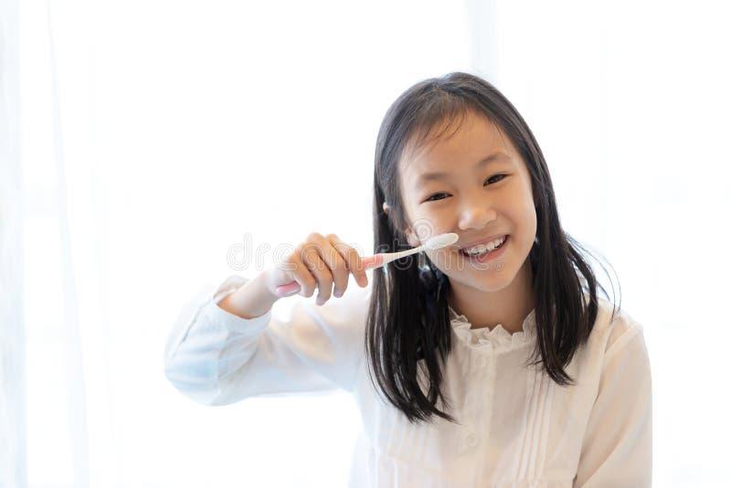 Den asiatiska flickan ler och rymmer en tandborste på vit bakgrund, sund tandconcep royaltyfria foton