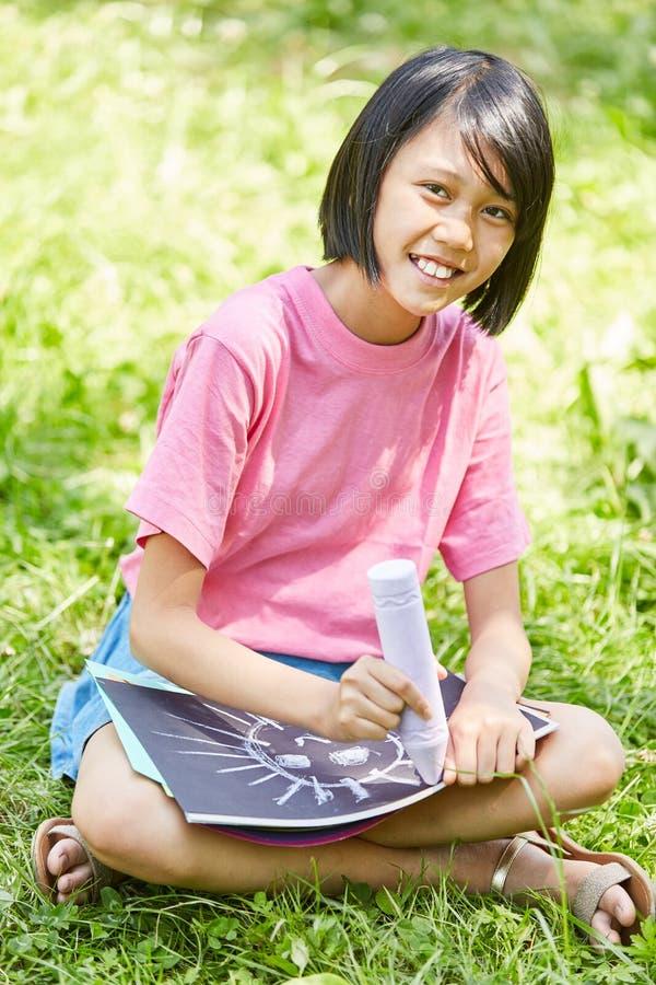 Den asiatiska flickan målar med krita arkivfoto