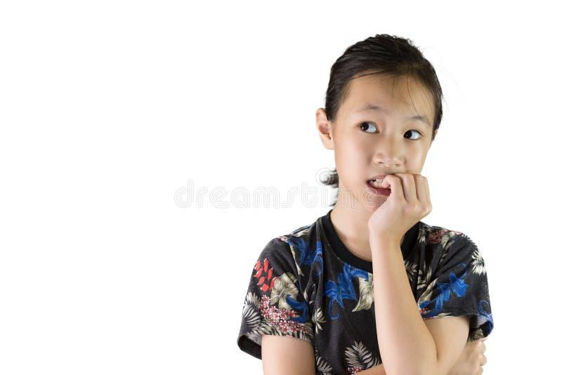 Den asiatiska flickan med nervöst uttryck och spikar att bita arkivfoton