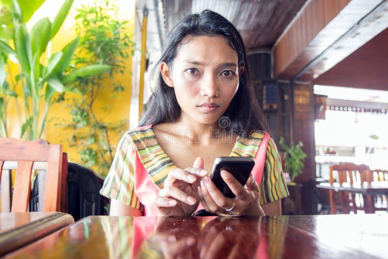 Den asiatiska flickan med telefonen royaltyfri fotografi