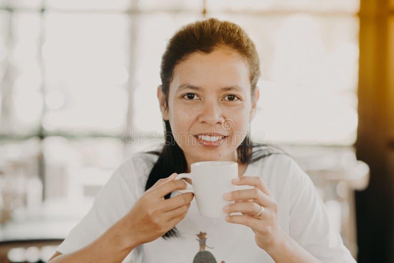 Den asiatiska flickan sitter för att dricka kaffe på en coffee shop arkivfoto