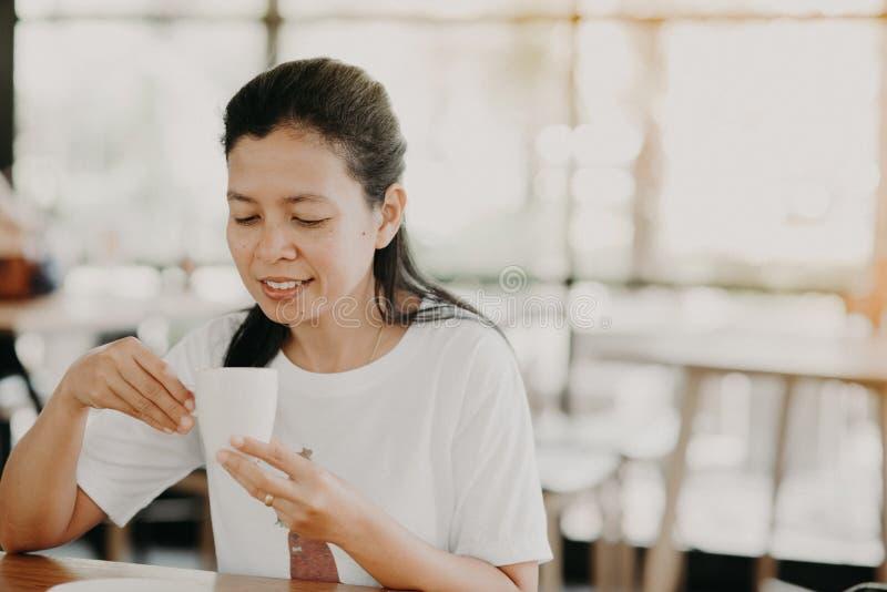 Den asiatiska flickan sitter för att dricka kaffe på en coffee shop royaltyfri bild