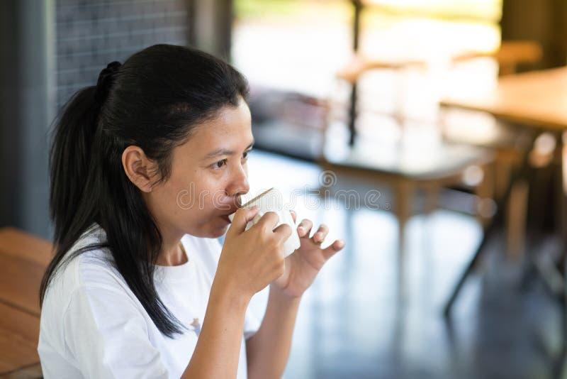 Den asiatiska flickan sitter för att dricka kaffe på en coffee shop fotografering för bildbyråer