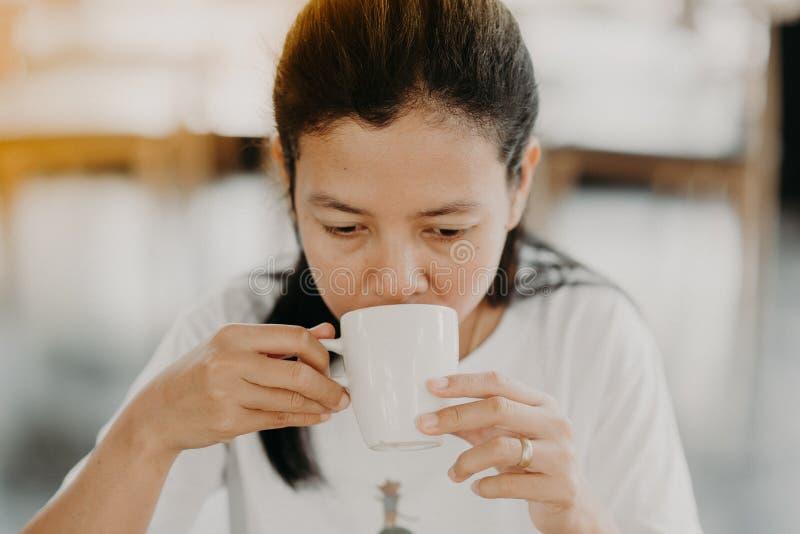 Den asiatiska flickan sitter för att dricka kaffe på en coffee shop arkivfoton