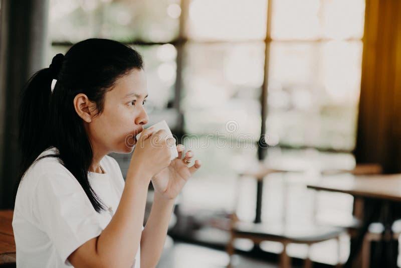 Den asiatiska flickan sitter för att dricka kaffe på en coffee shop royaltyfri foto