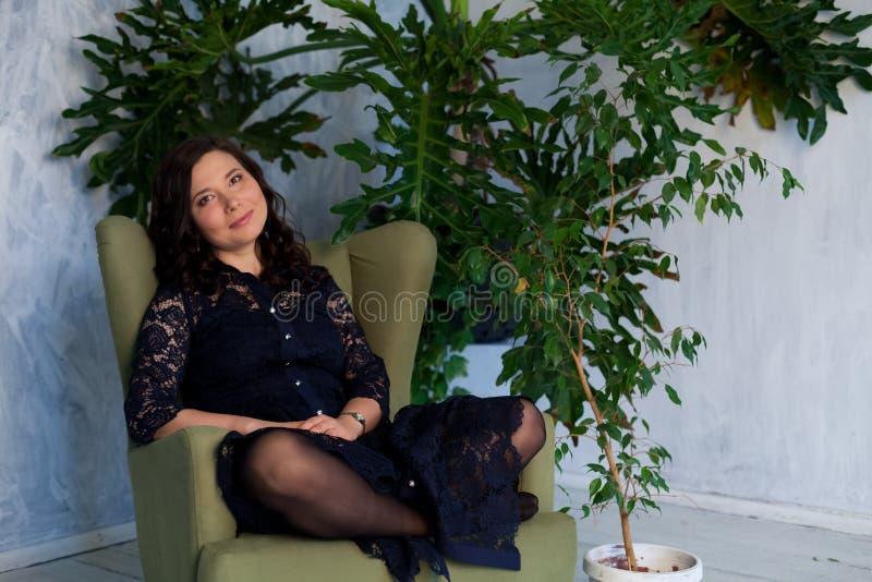 Den asiatiska flickan sitter i en grön stol på en husväxt arkivfoton