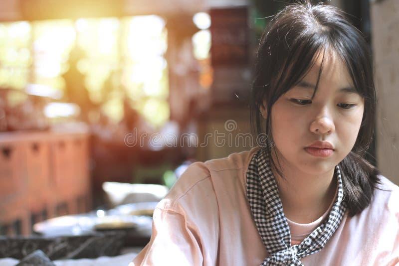 Den asiatiska flickan sköts jag oavsiktligt Medan vänta på kakan arkivbild