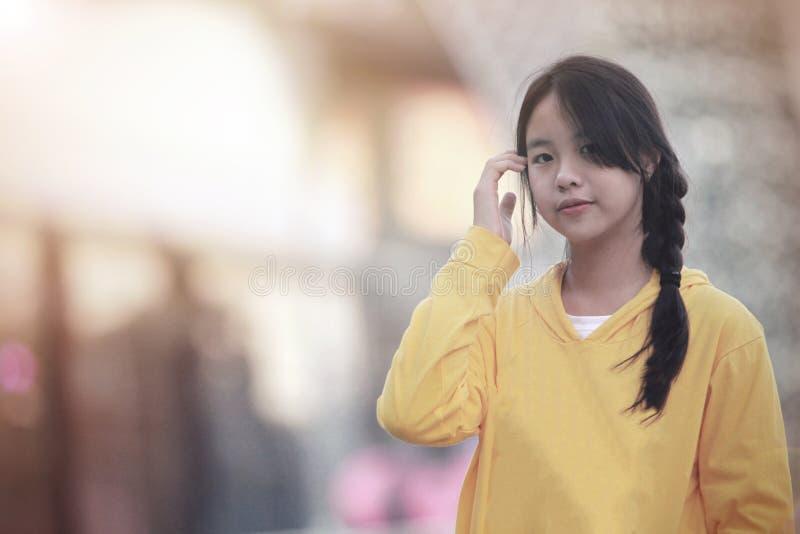 Den asiatiska flickan som rymmer en smartphone på ett ställe i Chiang Mai, Thailand arkivbild