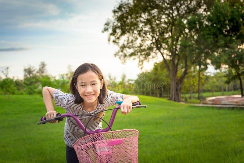 Den asiatiska flickan som ser kameran som ler med ett gulligt på cykeln i det utomhus-, parkerar, barnövningen i natur i morgonen fotografering för bildbyråer