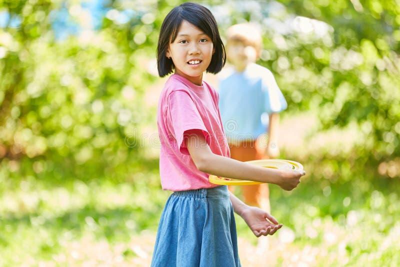 Den asiatiska flickan spelar frisbeen arkivbild